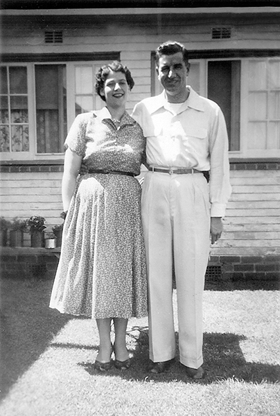 Old black and white picture showing two newly weds in front of new home.